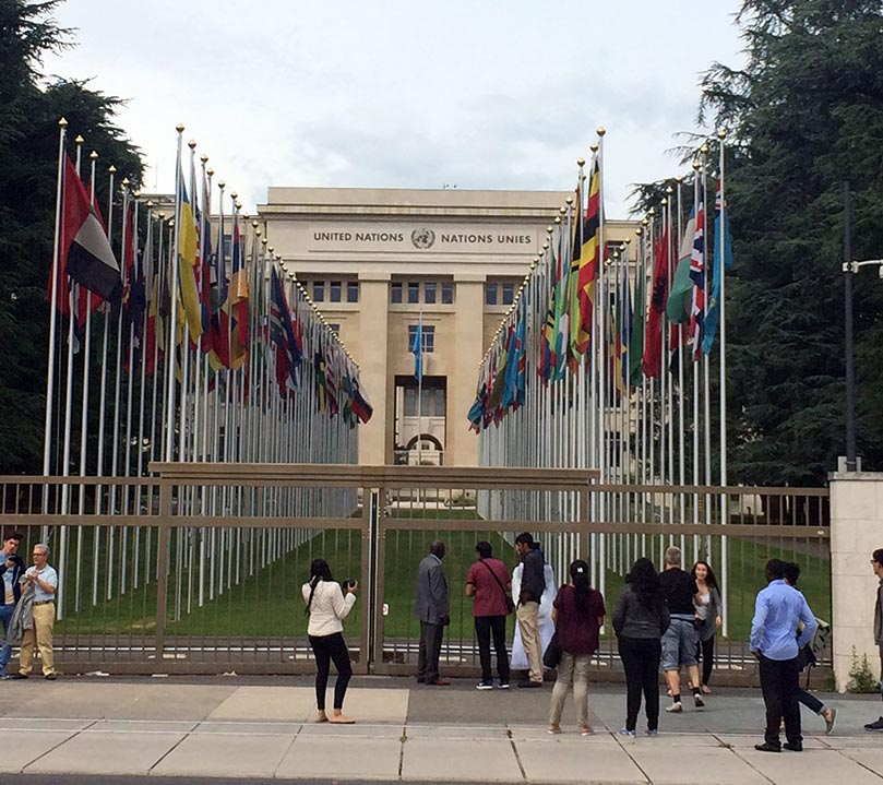 The outside of the UN building in Geneva, Switzerland with the flags of all the countries in a row outside of the entrance.