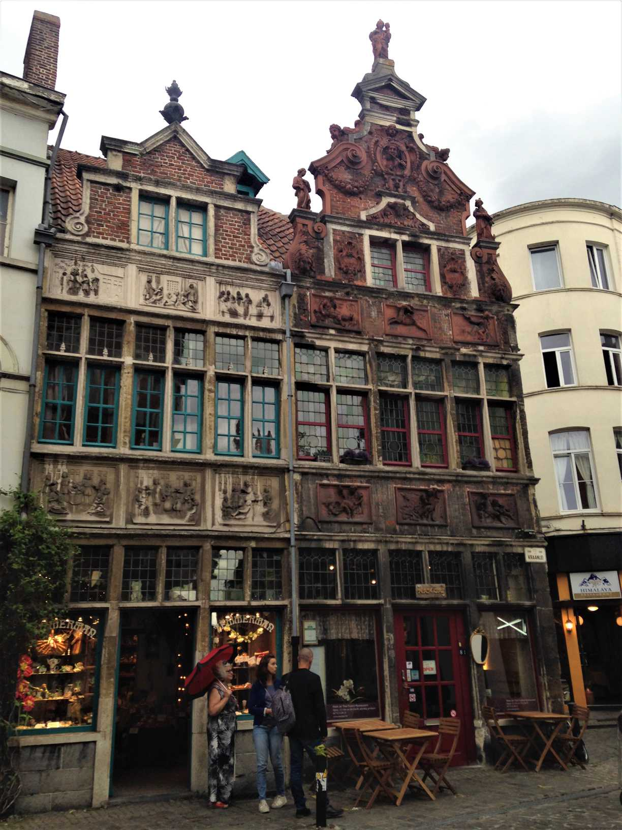 A picture of a unique brick building in Ghent, Belgium with stone carvings on the facade and gables. Tables and chairs are outside of the building, which is on a cobblestone street.