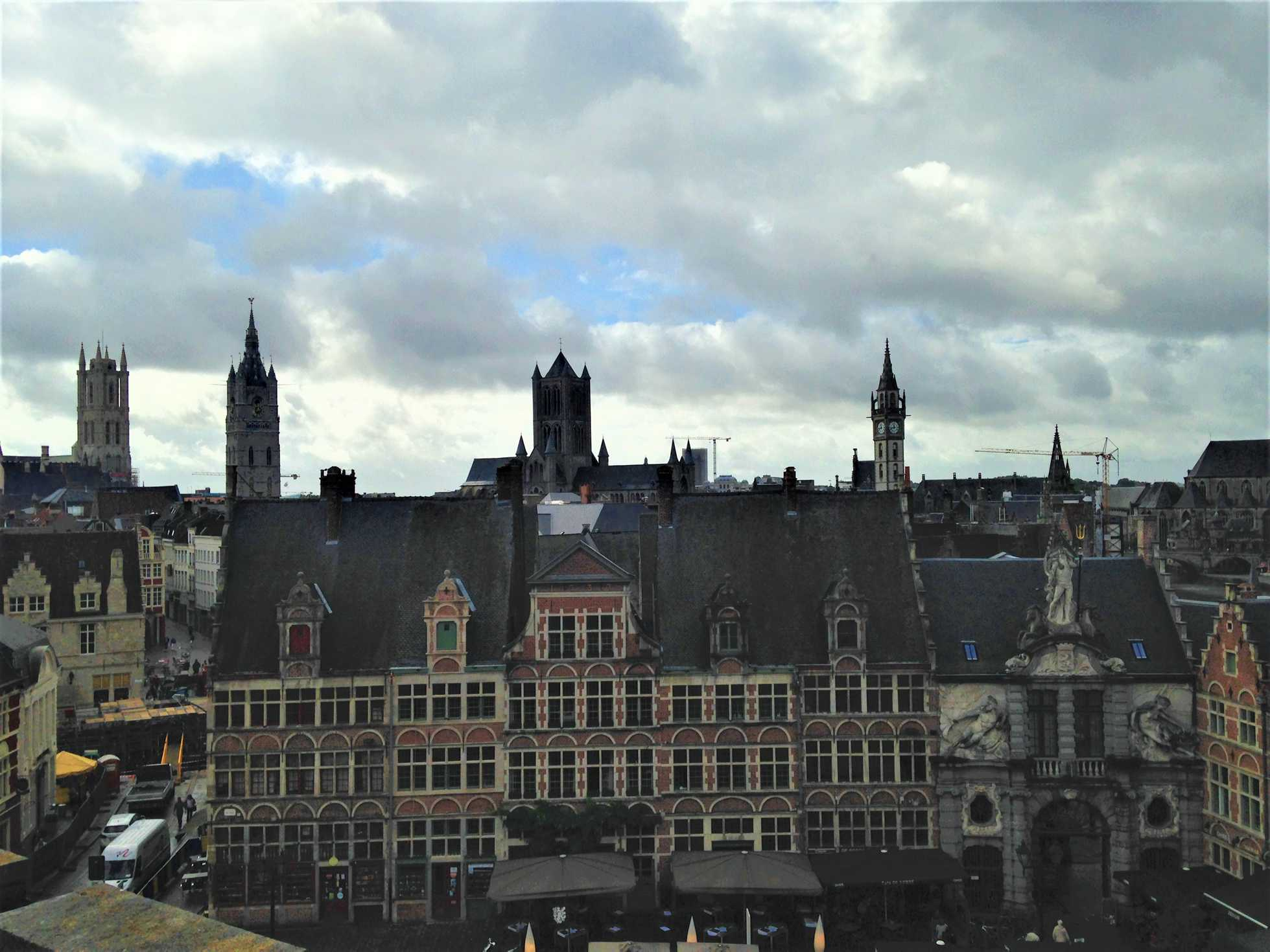 A picture of a square in Ghent, Belgium with the four towers of Ghent in the background.
