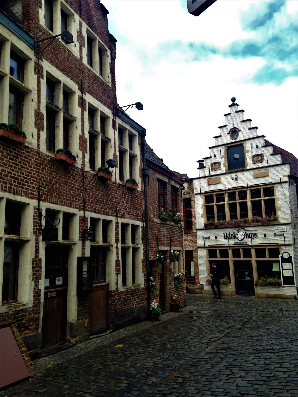 This picture shows a street in Ghent, Belgium with a brick building to the left and a white brick building with gables in the background.