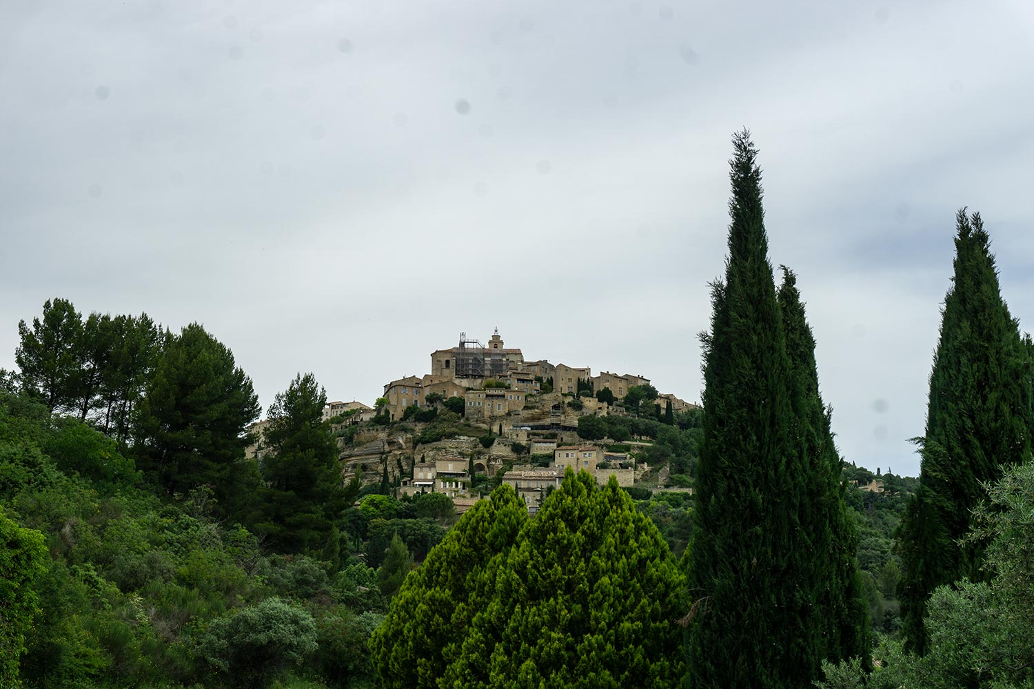 The town of Gordes in Provence, France on a hill as seen from a distance.