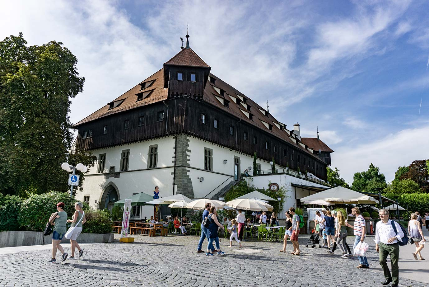 A medieval building in Konstanz, Germany that is half wood and half plaster. There are tables and umbrellas outside of the building.