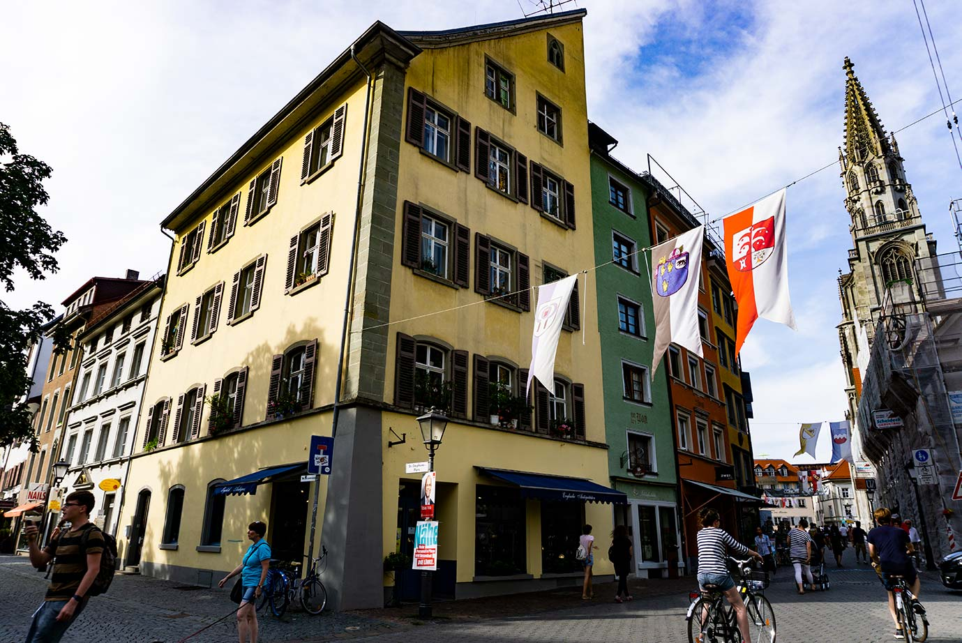 A street in Konstanz, Germany with medieval banners hanging and bicyclists below.