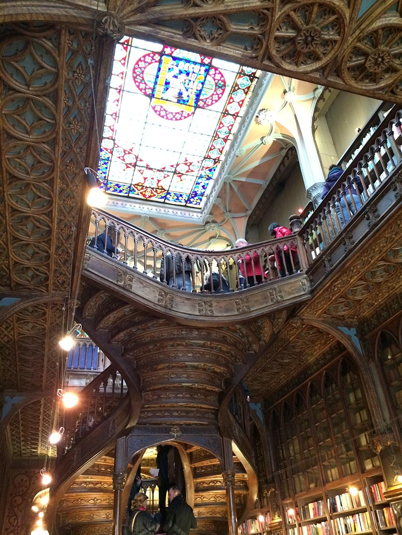 The interior of the Lello bookshop in Porto, Portugal. It is all wooden with a large stained glass window in the ceiling.