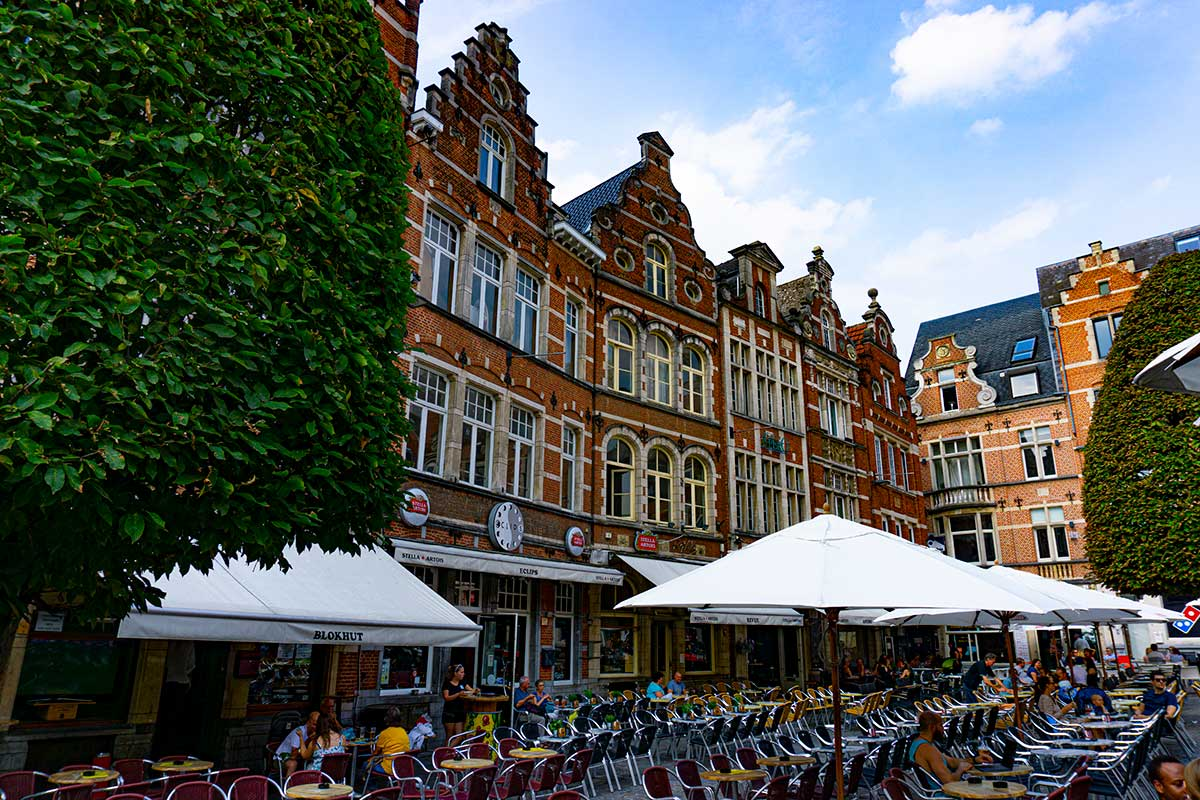 A town plaza in Leuven, Belgium lined with gabled buildings and bars.