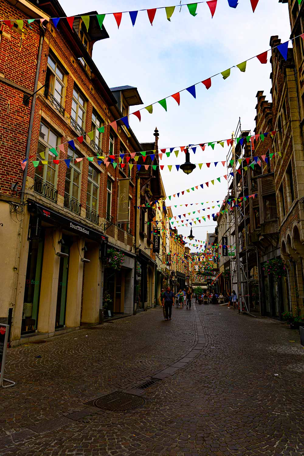 A street Leuven, Belgium lined with brick buildings with flags hanging between the buildings.