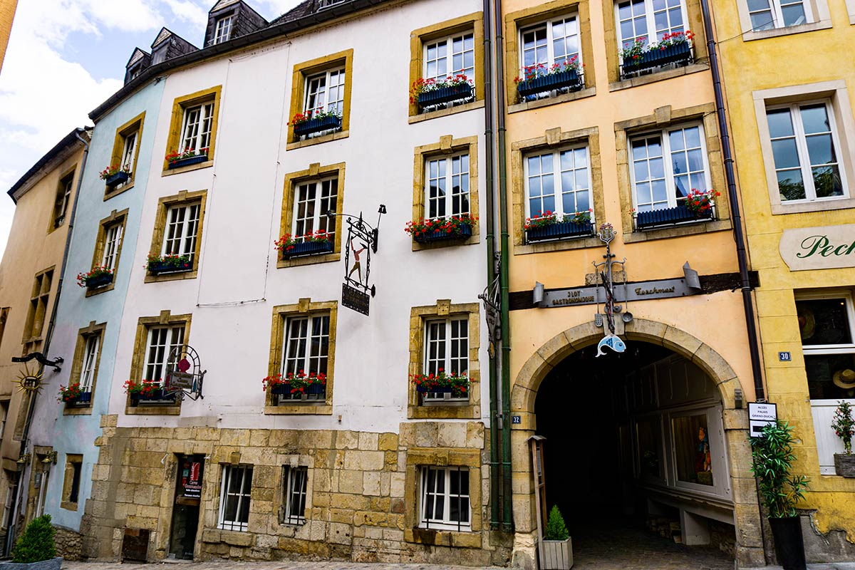 Old houses with flower boxes in the city center of Luxembourg City. Metal signs hang ourside of each building.