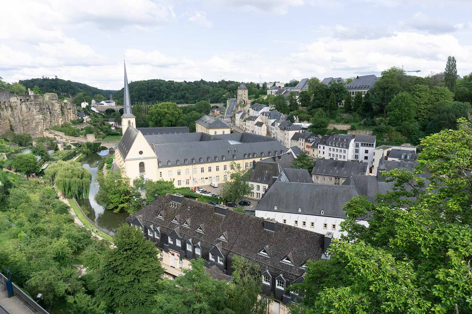 A view of the valley of Luxembourg and a church with a river running beside it.