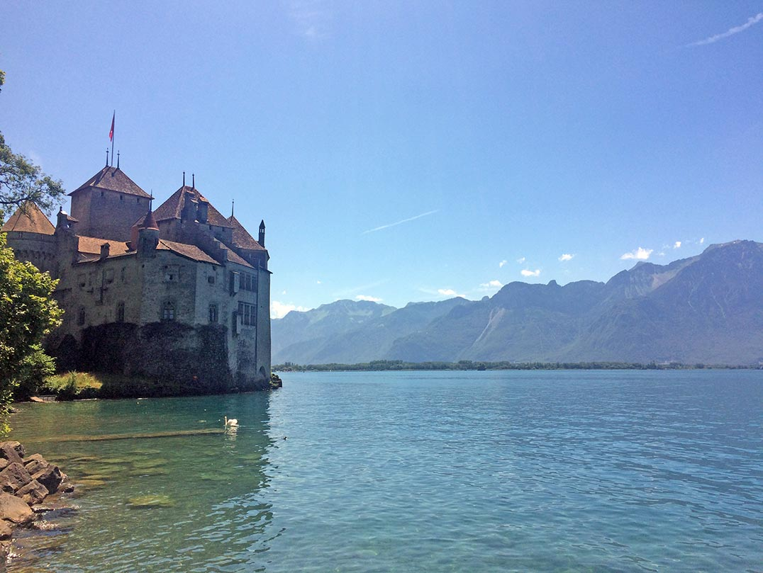 Chateau de Chillon in Montreux, Switzerland. The buidling is made of stone with a red roof and is situated right on the banks of Lake Geneva. The sky is a clear blue.