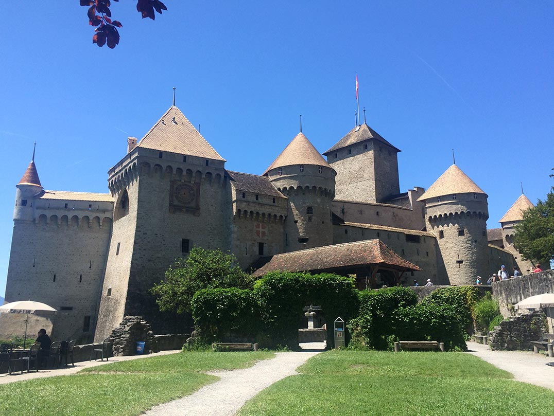 Another view of Chateau de Chillon in Switzerland. You can see a grassy area with the castle in the background.