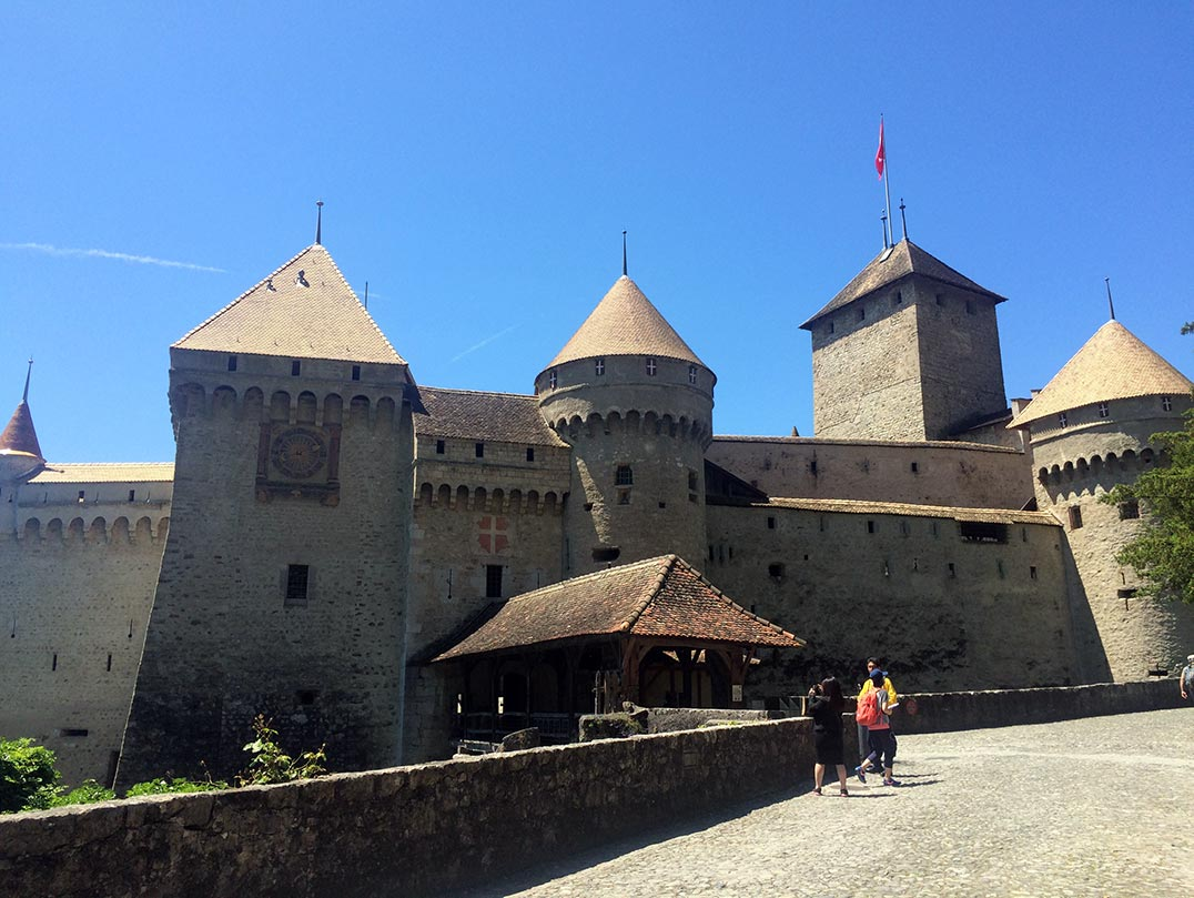 The facade of Chateau de Chillon in Montreux, Switzerland. The castle is made of stone and has many towers.