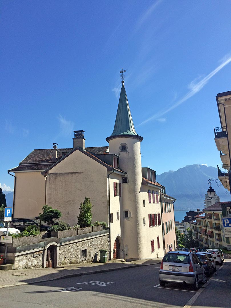 A white buiding with a turret and a pointed roof in Montreux, Switzerland. Mountains can be seen at the end of the street.
