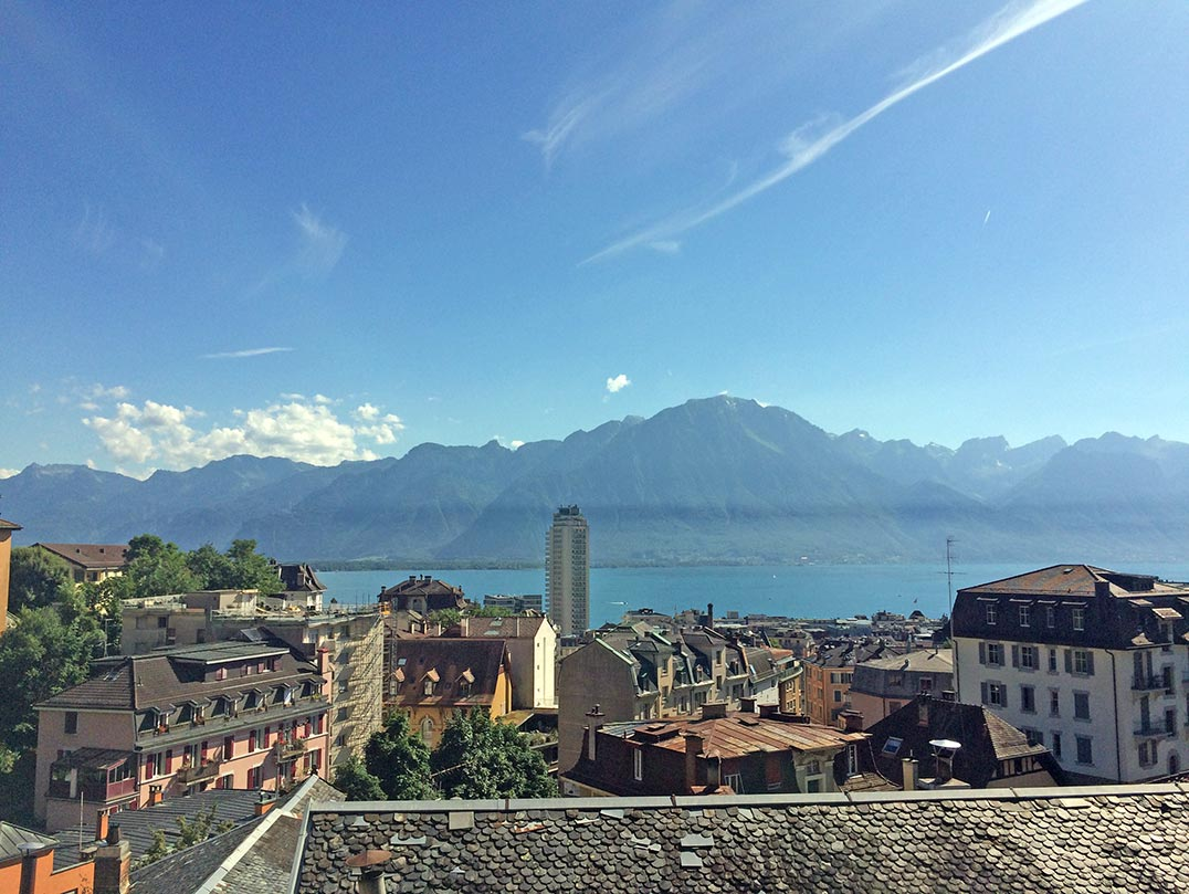 A bird's eye view of Montreux, Switzerland. You can see buildings and the lake with mountains in the distance.