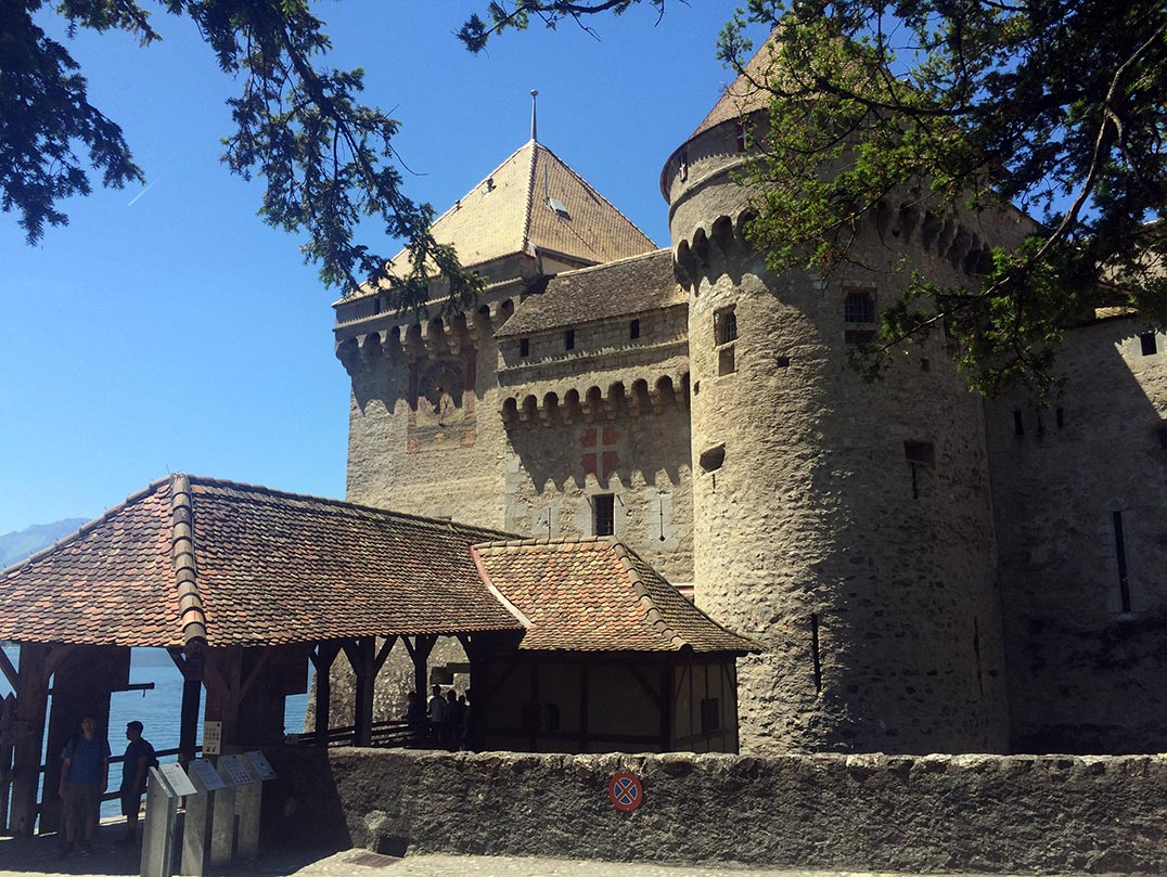 The entrance to Chateau de Chillon in Montreux, Switzerland. You can see a covered bridge leading to the entrance of the castle. the castle is made of stone and has a round tower and a square tower with a clock.