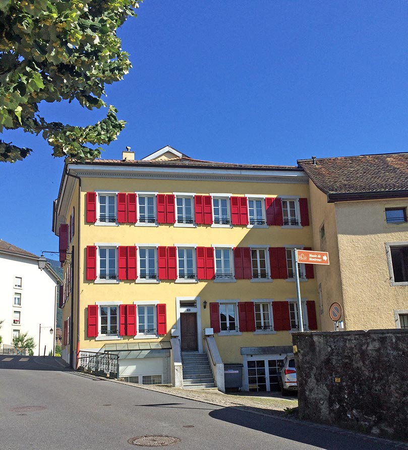 A big traditional Swiss house in Montreux, Switzerland. The house is yellow with red shutters and stairs leading to a brown door. There is a clear blue sky.