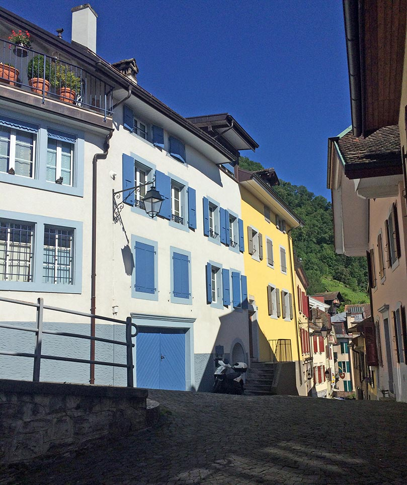 Colorful houses in Montreux, Switzerland. The house in the forefront is blue and white, the house next to it is yellow and green and the house across the street is pink and maroon. A hill with trees can be seen at the end of the street.