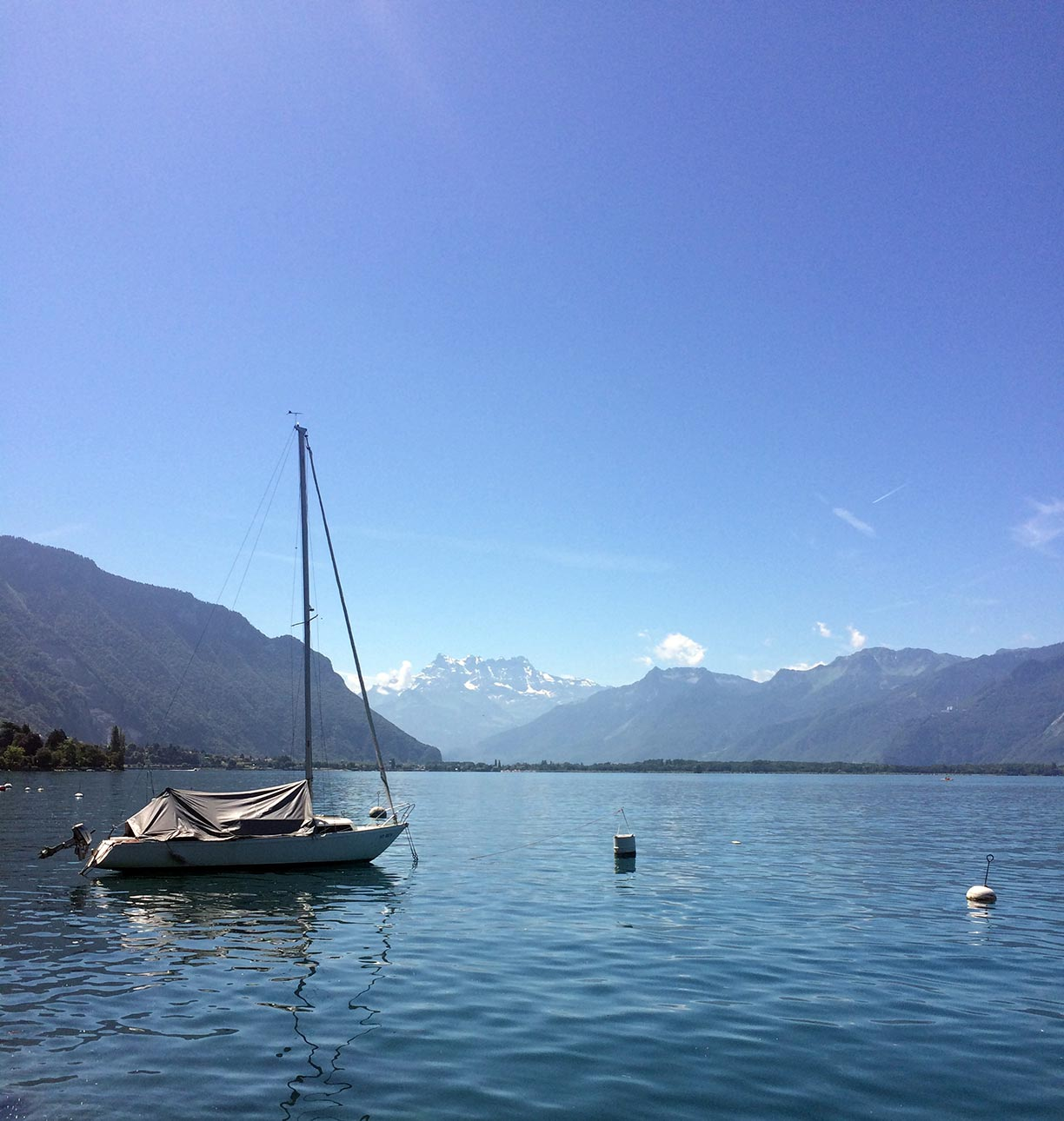 Lake Geneva with views of snowy mountains in the distance. A sailboat is in the foreground to the left.