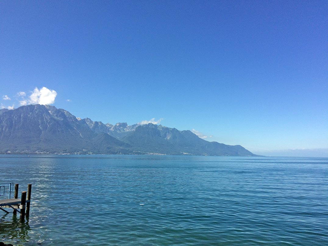 Lake Geneva with views of mountains and a blue sky.