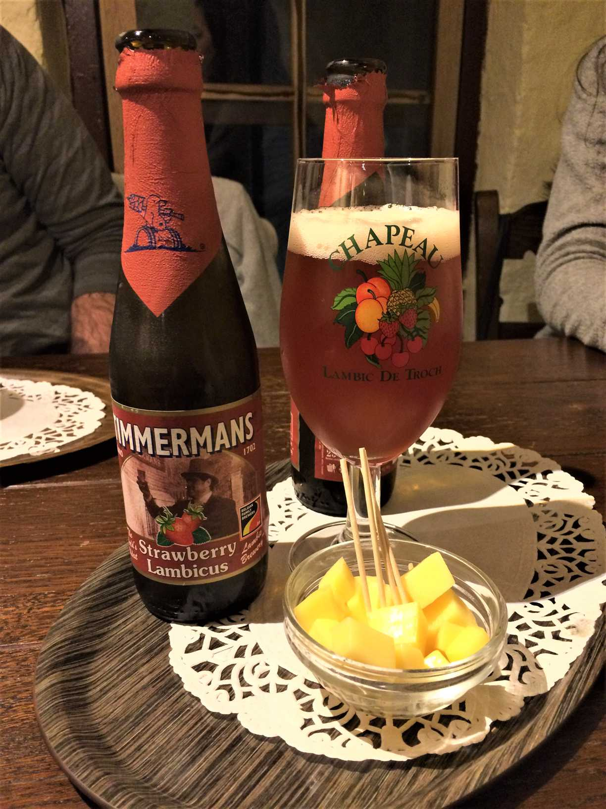 This picture shows two bottles of Zimmermans strawberry lambicus beer, a glass of beer, and a small bowl of cubed cheese with toothpicks sticking out.