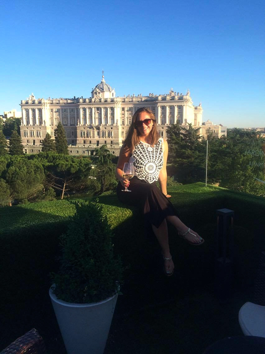 Picture of a girl at a rooftop bar in front of a palace in Madrid, Spain.