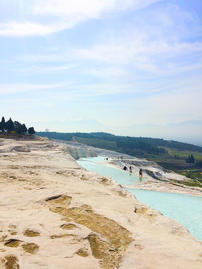 A turquoise lake and the white hills of Pamukkale in Turkey.