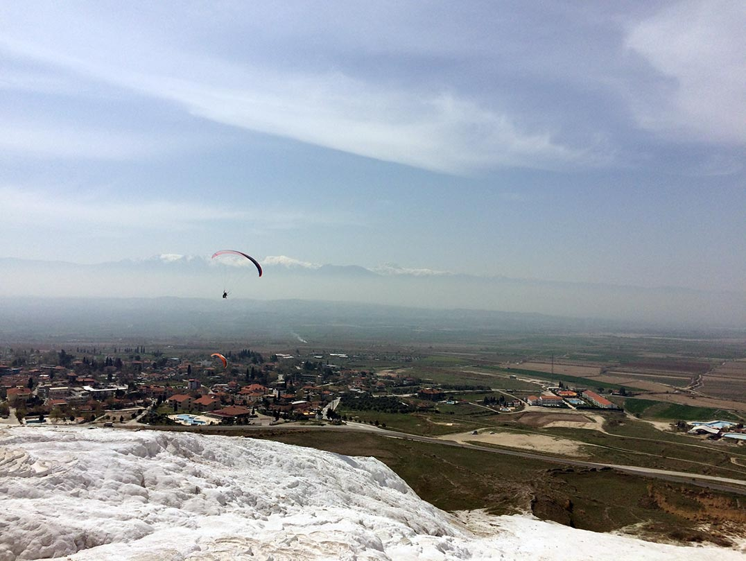 A paraglider and the white hills of Pamukkale in Turkey.