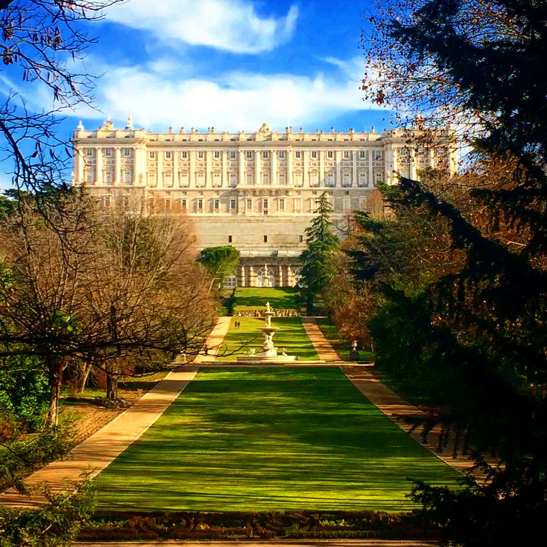 A picture of the royal palace of Madrid from Moro Park with a blue sky.