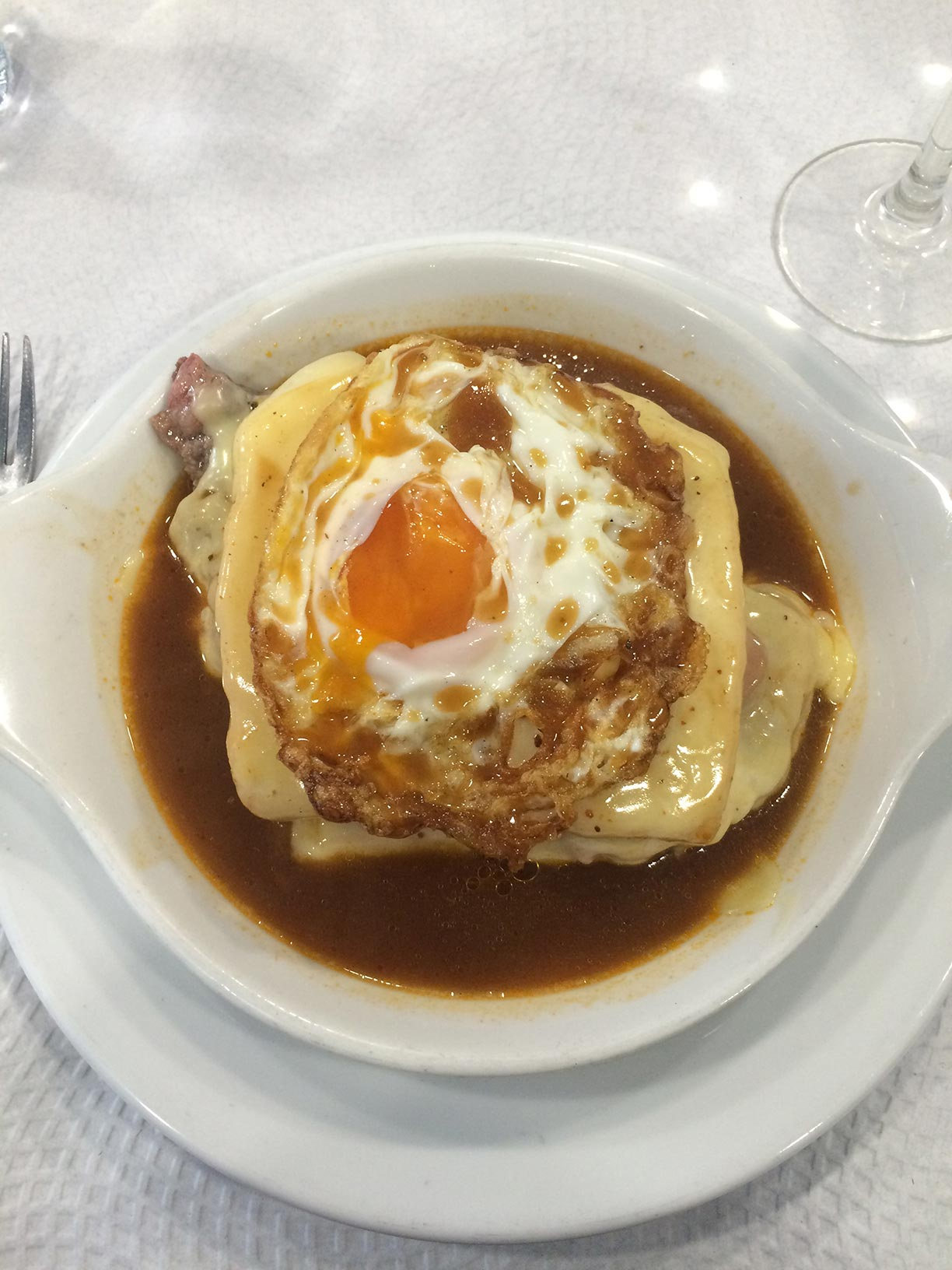 The famous Francesinha sandwich in Porto, Portugal with an egg on top and soaked in gravy.