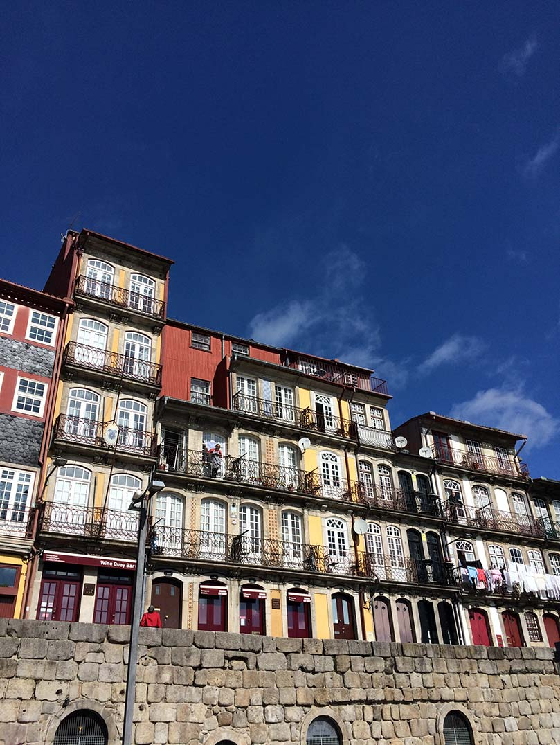 Colorful multi-storied houses lining the riverbank in Porto, Portugal.