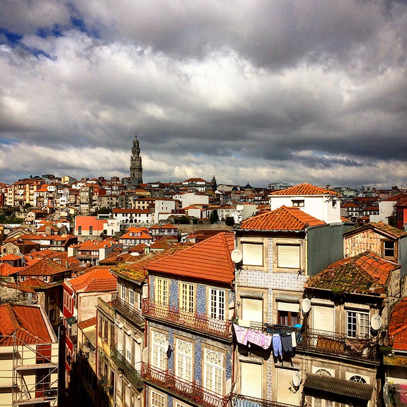 The colorful houses of Porto, Portugal and a tower in the distance on a cloudy day.