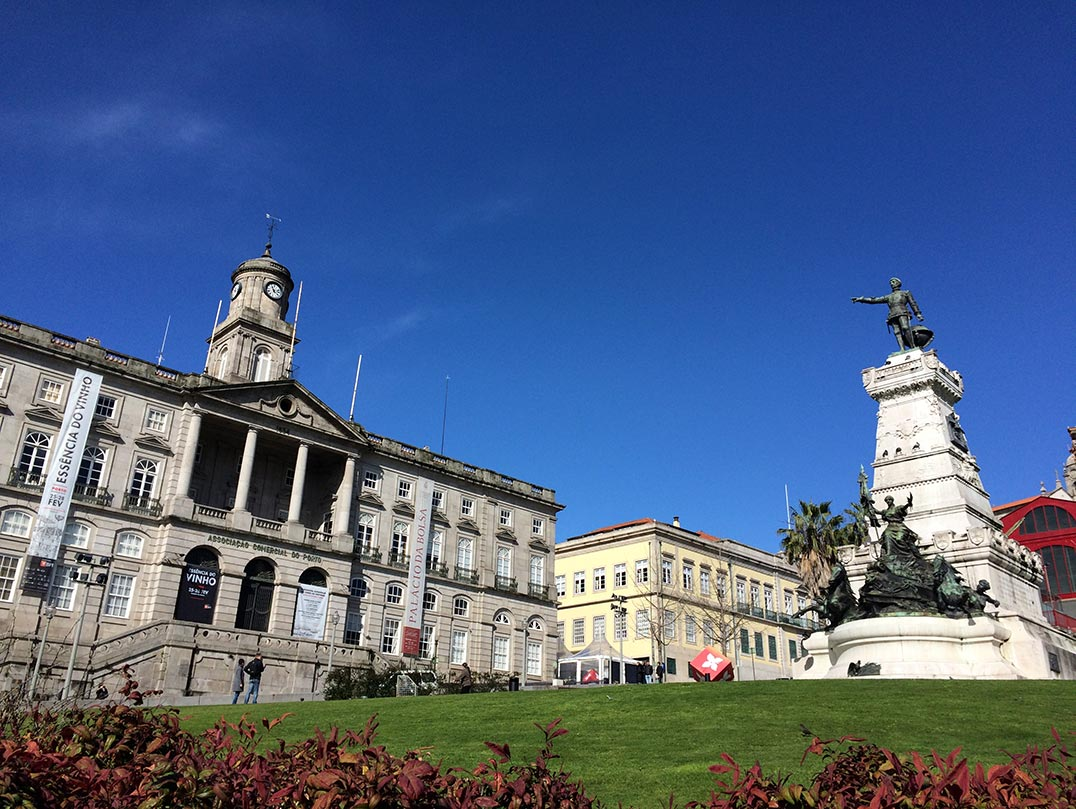 The outside of the Palacio da Bolsa in Porto, Portugal, as seen from a park with grass and a statue.