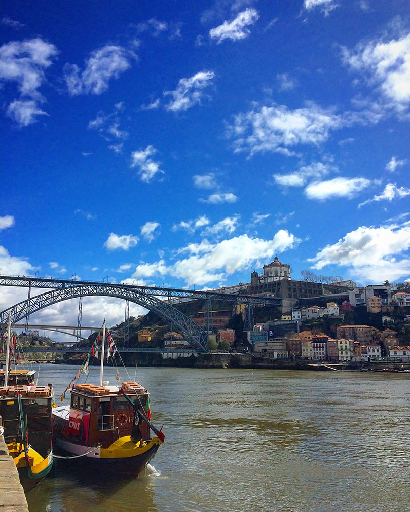 The banks of the Duero River in Porto, Portugal. There is a bridge in the background and a small red and yellow boat in the foreground.
