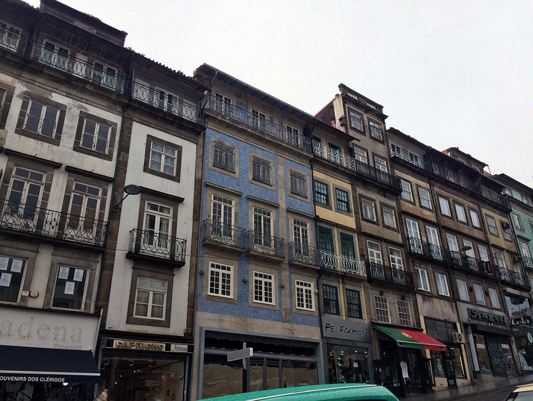 A street in Porto, Portugal with tiled buildings and store fronts.