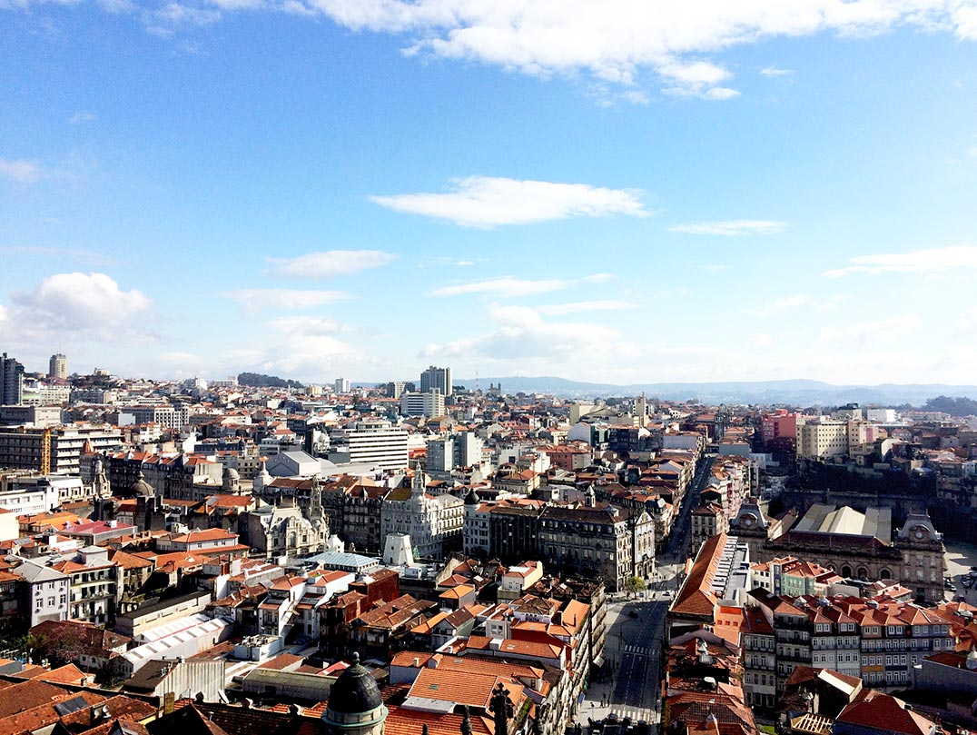 The view from a church tower in Porto, Portugal. You can see red tiled roofs and mountains in the distance.
