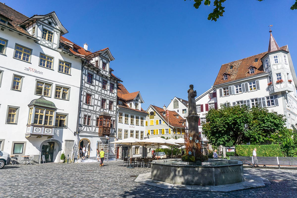 A charming plaza in Saint Gallen, Switzerland with colorful timbered buildings and a statue in the center.