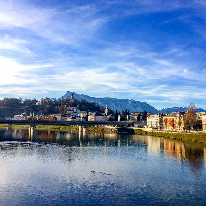 A lake with a the town of Salzburg, Austria behind it and mountains in the background.