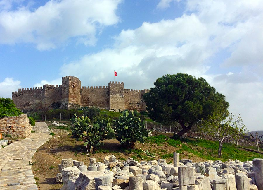 Ruins outside of castle in Selcuk, Turkey with the Turkish flag in the distance.