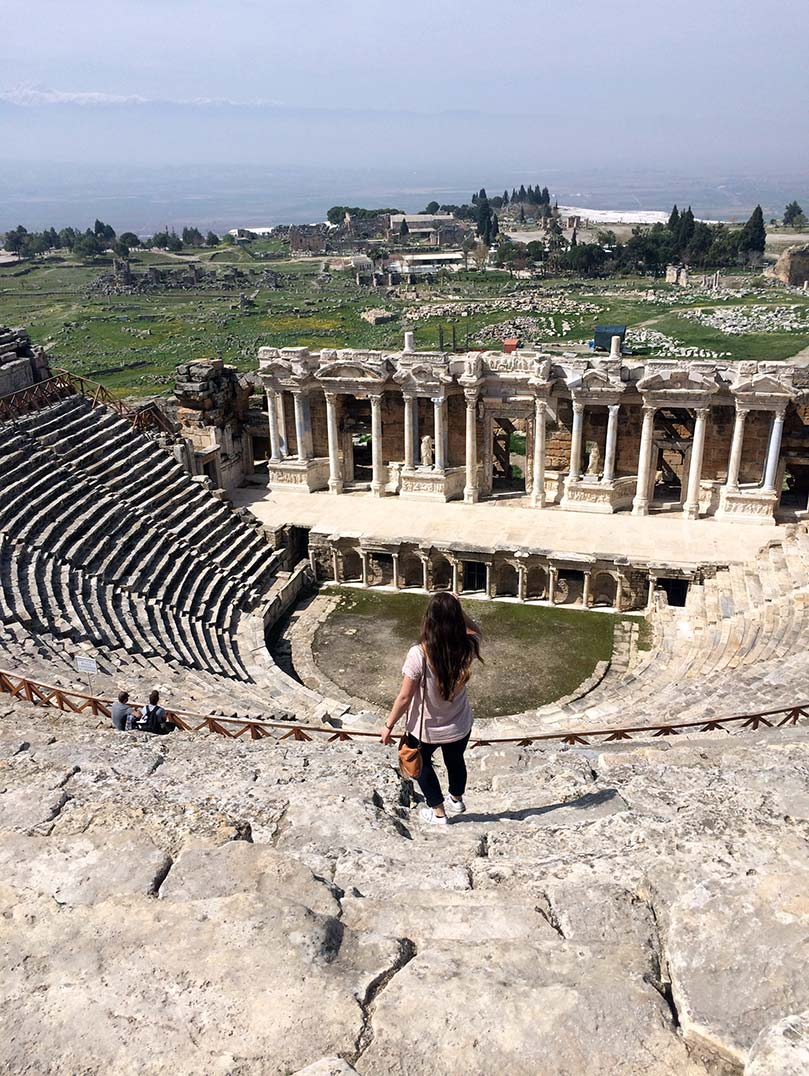 A girl standing in front of the ruins of a ampitheatre in Hierapolis, Turkey.