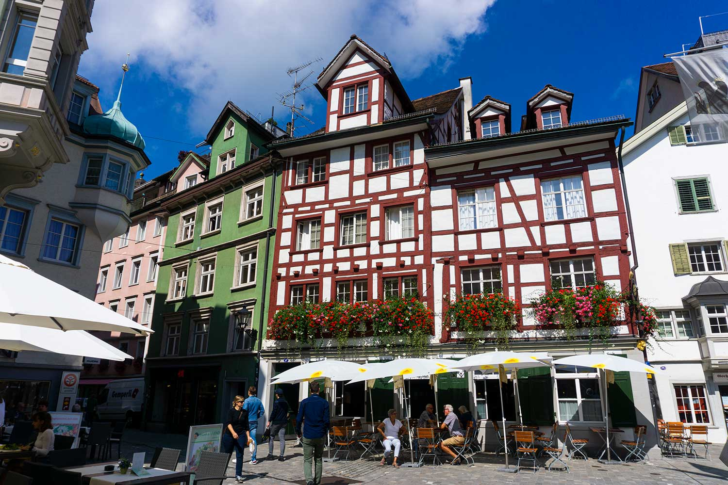 A colorful timbered building in St. Gallen, Switzerland with flowers in the window boxes.
