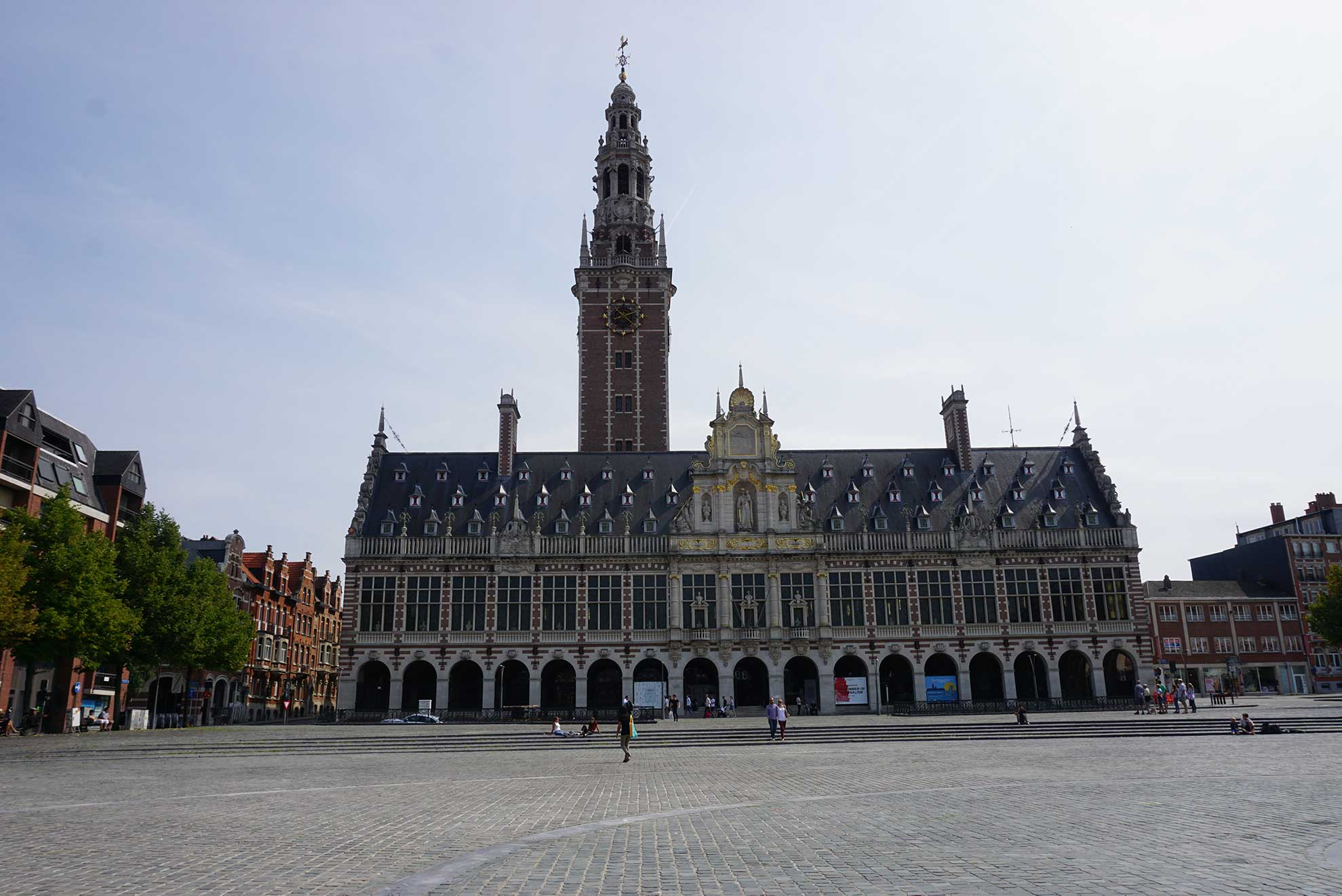 A building in a plaza in Leuven, Belgium with a tower.