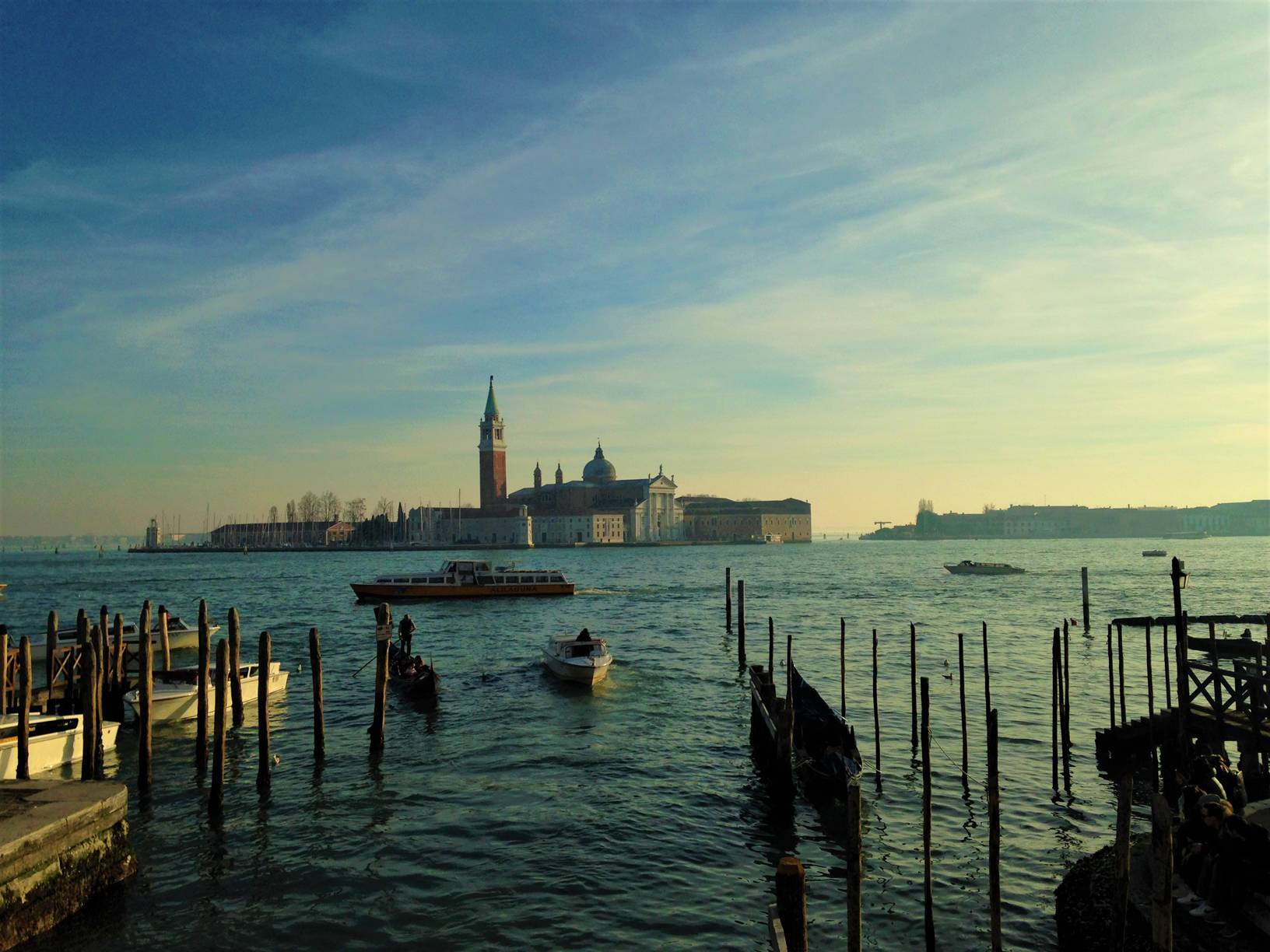 View of San Giorgio Maggiore from across the sea near St. Mark's square in Venice, Italy. Boats and gondolas are seen in the sea.