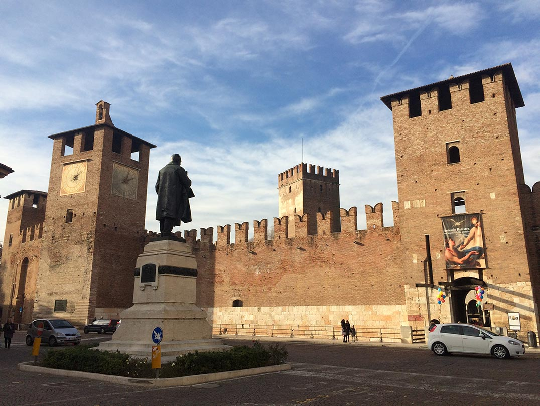 A castle in Verona, Italy with towers and a statue in front of it.