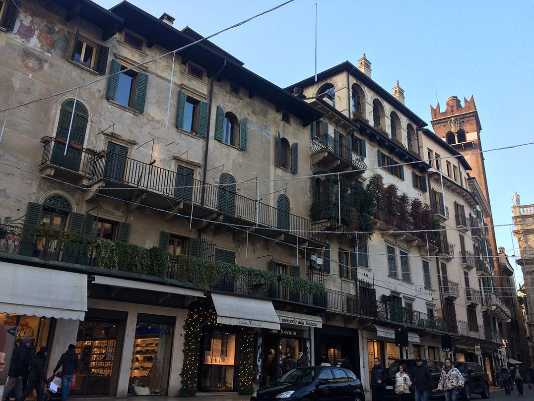 A street in Verona, Italy lined with old buildings with plants hanging from the windows.