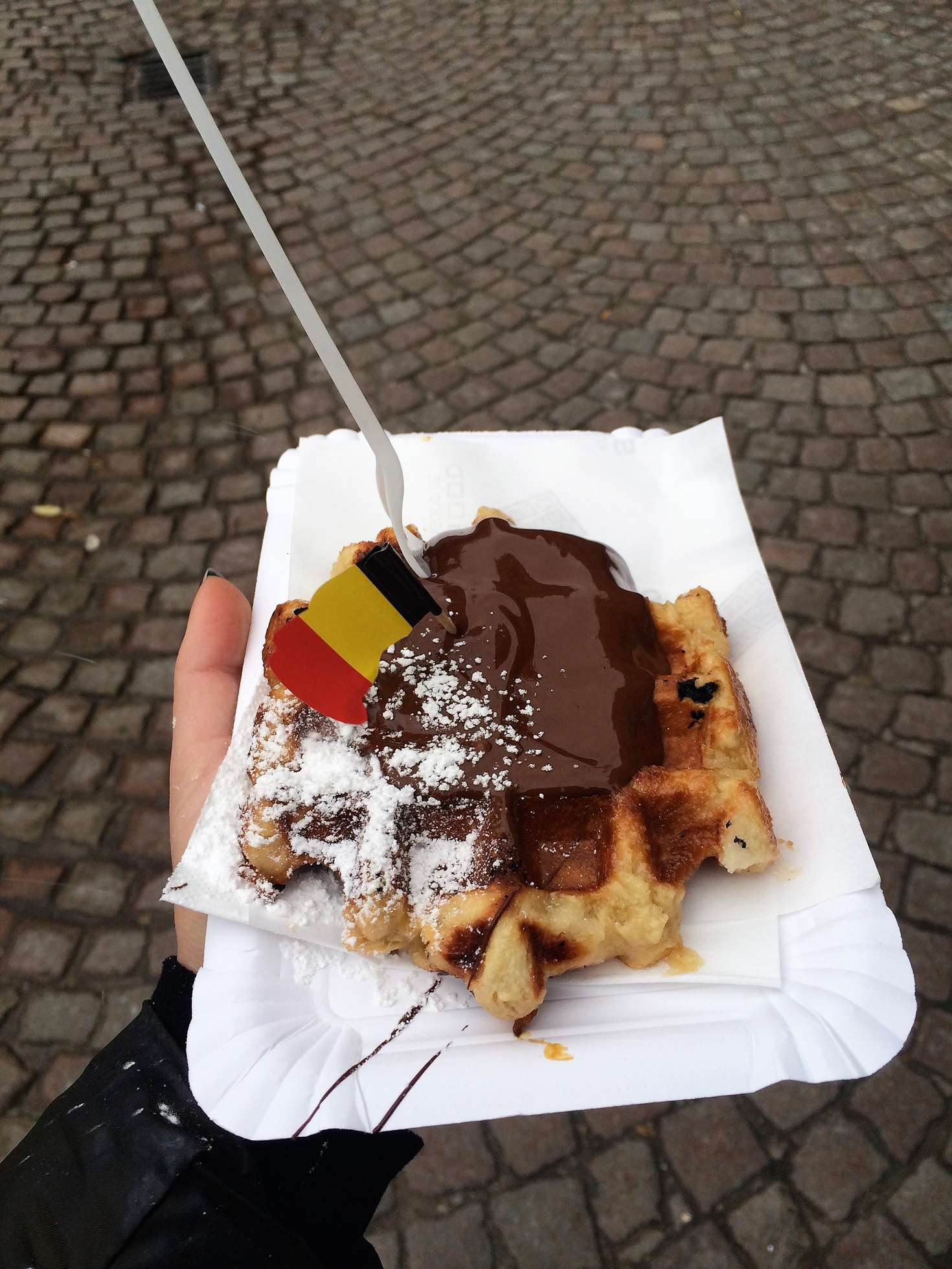 A picture of a liege waffle covered in nutella and topped with powdered sugar and a Belgian flag in Bruges, Belgium.