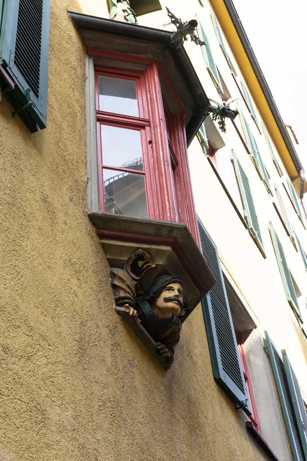 A carved face looks out at the streets from below a window in Konstanz, Germany.